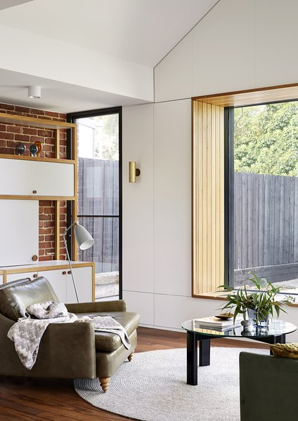 A timber window seat is surrounded by secret storage cabinets, adding functionality to otherwise unused space.