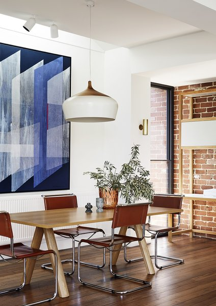 A Coco pendant from local designer Coco-Flip hangs above a wood dining table. The natural hues from the timber flooring and recycled brick blend with the warm furniture tones.