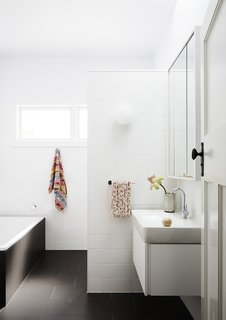 A full bathroom now fills part of the original living space. Dark Fiandre floor tiles contrast with a mix of bright white matte and gloss wall tiles. A Glo Ball wall sconce from Flos is the perfect playful addition to this modern bath.