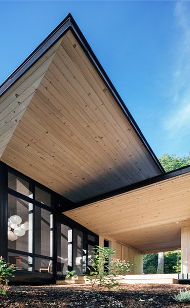 The large overhangs add drama to the cottage's simple form with far-reaching timber-clad planes.