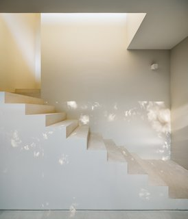A white, geometric stair is a bright contrast to the black exterior.