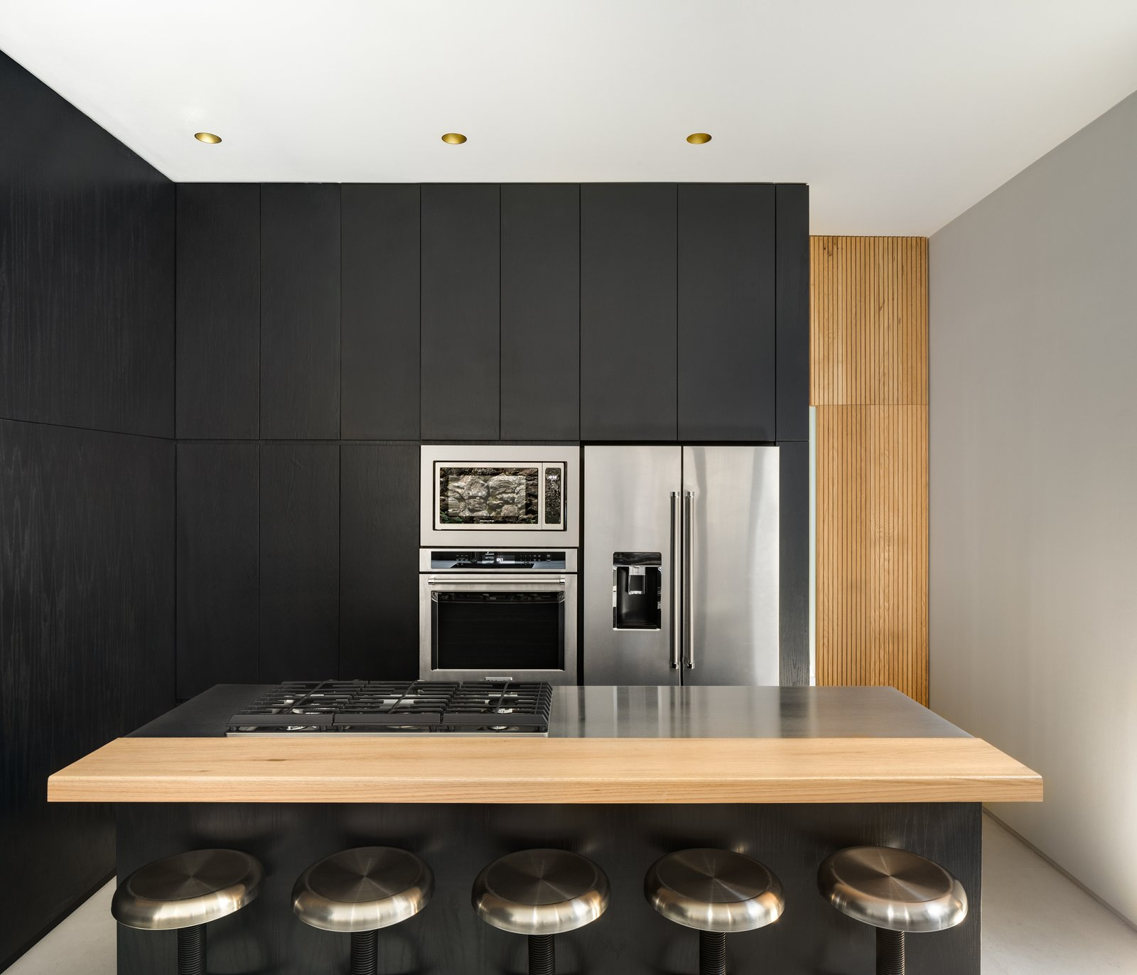 Lluvia by PPAA black kitchen with stainless steel and wood accents