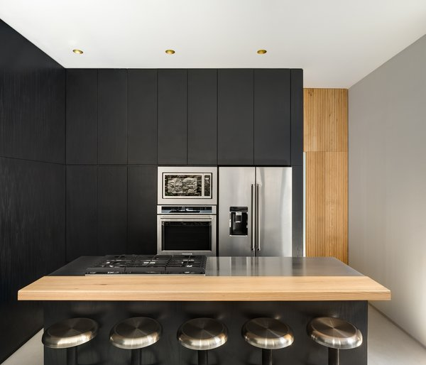 White oak details add a touch of warmth to the black kitchen while stainless-steel stools, countertops, and appliances bring an industrial edge.