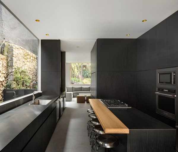 In contrast to the otherwise white and bright rooms, the kitchen resonates with the black exterior. Lacquered MDF cabinetry is sleek and seamless.