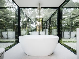 The freestanding tub provides views of the forested land.