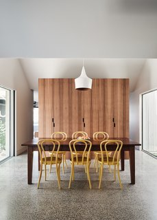 Simple wood joinery provides a nice backdrop to the muted dining area while also discreetly concealing a bathroom behind and within. A salt-and-pepper finish on the concrete slab carries throughout the main floor plan.