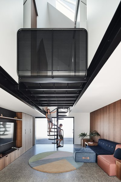 A spiral staircase leads to a bathroom and three bedrooms above. A perforated steel landing connects the bedrooms above and bridges a double-height main living space.