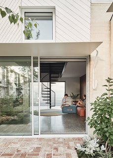 Large openings directly connect the interior living spaces with the garden. A thin metal canopy includes a special detail on which items can hang.