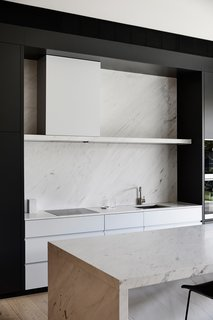 The kitchen pairs simple joinery and sleek fixtures with natural materials—like the elegant stone island and backsplash. The concealed hood and simple stone shelf keeps the design clean and tidy along the cooking prep area.