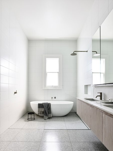 The bathrooms remain light and bright with classic white ceramic wall tile, pale oak cabinetry, and Fibonacci Stone floor tile.