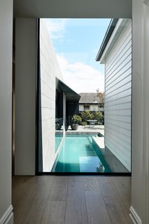 A large floor-to-ceiling window provides uninterrupted views to the rear garden and lap pool, while visually marking the transition from old to new.
