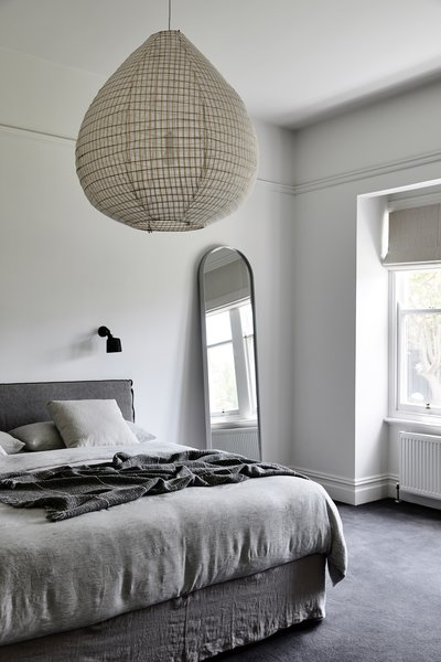 The bedrooms are located in the more private front of the home. The original trim, windows, and casing remain, paired with modern furnishings and textiles. Here, a large decorative pendant light from Hub Furniture and a rounded floor mirror from Biasol Design serve as subtle accents.
