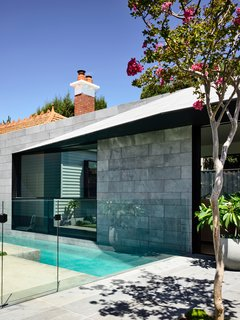 The original chimney peeks above the new rear addition. Throughout the design, there is a play of tactile elements which blend old and new.