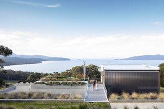 Approaching the home from above, guests encounter a green roof that feels united with the landscape beyond. The entry sequence presents purposefully framed views that hide and reveal the lake.