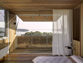 Layered facade materials allow for cross ventilation, protect from the sun, and add privacy. In the master bedroom loft, wood screens create an opportunity to be outdoors without becoming too beaten by the sun, and white curtains create another gauzy partition.