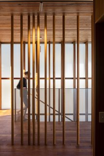 Vertical wood post act as a screen between circulation and sleeping spaces. An exterior, double-height wall of translucent Rodeca cladding extends along the staircase, leading you to the master bedroom loft.