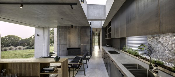 Located on the ground level, the kitchen and main living space are open to the elements. Large sliding doors pocket into the wall cavity, providing a seamless connection to the coast. Skylights allow natural light to filter into the space while providing glimpses to the green roof above. A horizontal window provides a snapshot to the rugged, mountainous terrain. The linear kitchen leads along a circulation spine, which connects to the more private areas.