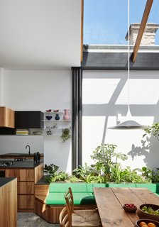 A garden is integrated into a green bench seat, optimizing space in the dining area while drawing the outdoors in.