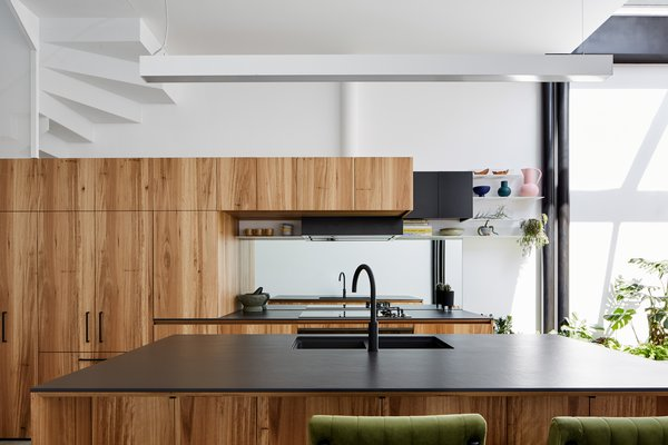What was once a closed-off kitchen has been transformed into an efficient cooking and dining space complete with simple wood cabinets, sleek fixtures, and black accents. A mirrored backsplash reflects light, making this open space feel even larger.