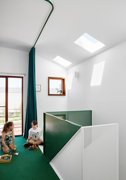 A flexible loft space at the top of the stairs doubles as a sleeping area when the curtain is closed, and a playroom for the kids. Skylights and punched window openings allow natural light to filter into these upper-level living spaces