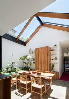 The existing dining room ceiling and a leafy roof deck outside the main bedroom were demolished. In their place, a large pitched glass roof with sliding awnings was installed, completely transforming this once dark and cramped terrace home.