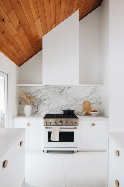 "A 36"" matte white Cafe Appliance range with metal hardware is paired with a dramatic marble backsplash and concealed range hood with a drywall surround."