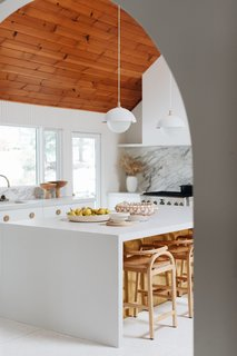 Paired with white, the wood ceiling is no longer an eye sore but a touch of warmth in this subdued and serene kitchen space.