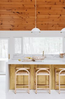 Brass panels decorate the back face of the island, drawing in Sarah's personal metal touch. Wood counter stools from The Citizenry provide the perfect wood accent which connects to the warmth of the wood ceiling above.