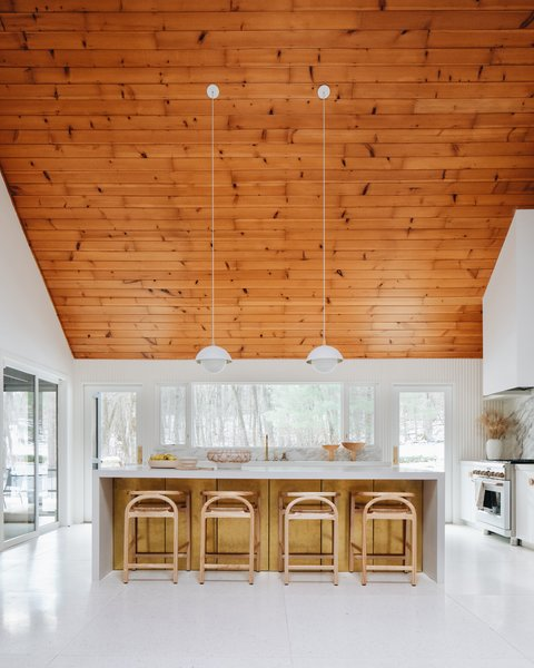 The warmth and softness of the wood ceiling is brought down to the cabinets with elegant touches such as the brass island panels, wood counter stools, and wood hardware.