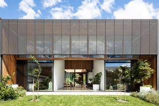 Perforated steel screens provide shading and privacy to the interior living spaces. The garden extends from the inner courtyard to the rear yard with open, connected spaces.