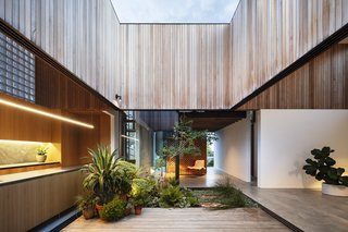 Quadrants are outlined by cedar-clad bands which slice through the ceiling and extend out to meet the courtyard's cedar cladding.