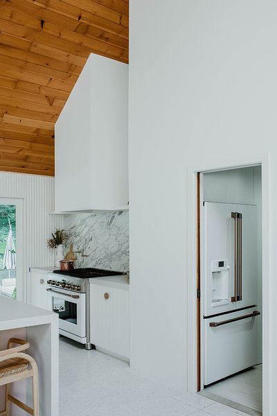 Previously, a small bathroom was located off the kitchen space. By relocating the bathroom elsewhere in the home, this freed up space for a large walk-in pantry where all the food and clutter could hide, and even the fridge.