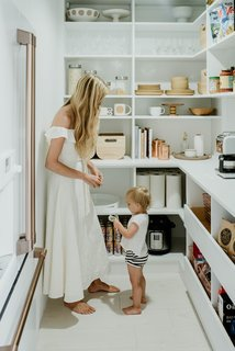 With the help of California Closets, the homeowners maximized every square inch of space with shelving, drawers, and a countertop area for placement of various small appliances like a microwave, coffee maker, and tea kettle.