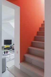 Orange Aurora walls edged in crisp white lend a striking effect to the staircase leading to the upper floor. Minimizing this bold color intervention to a small area allows the stair to serve as a focal point without overwhelming the design.