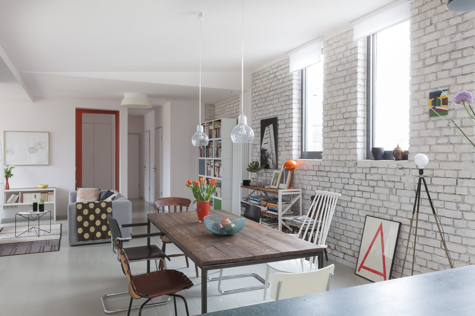 Dining Room, Table, Lamps, Pendant Lighting, Chair, Ceiling Lighting, and Accent Lighting Before the renovation, brick walls and lackluster wooden floorboards suffocated the space. The design team introduced bright, neutral finishes.  Photo 1 of 19 in A Historic Berlin Apartment Is Transformed Into a Colorful Live/Work Home