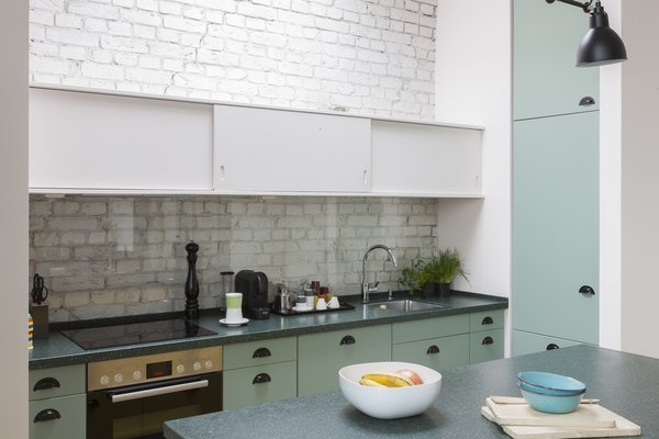 In the kitchen, lemon-yellow and mint-green cabinets complement the forest-green granite countertops. White overhead cabinets blend in with the white brick backdrop.