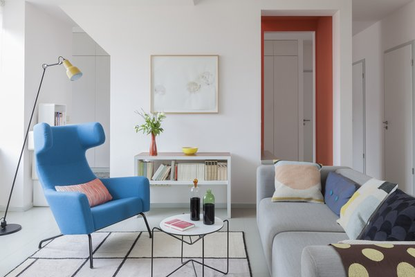 The living area has a bold, contemporary look with subdued, neutral tones providing a backdrop for small pops of energetic colors.