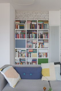 White walls serve as a backdrop for bold pops of color provided by furnishings, accessories, and books.