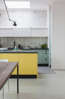 Colored wall cabinets and a kitchen island structure the open-plan cooking area. White-painted bricks and a large skylight keep the space bright.