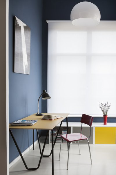 原色简单的办公家具站出来反对海洋蓝色的墙壁和白色的窗帘。