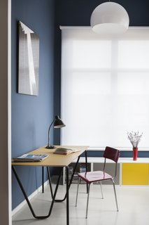 Simple office furniture in primary colors stands out against marine-blue walls and a white window shade.