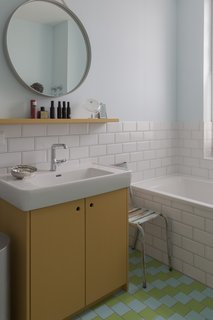 In the bathroom, two-toned floor tiles add a playful aesthetic which pairs nicely with standard white subway tile and light-blue walls.