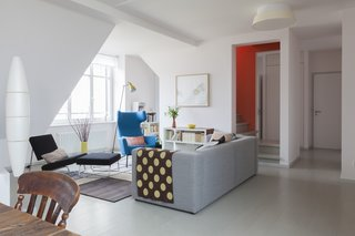 Graphic and pastel textiles adorn a collection of modern chairs and sofas in the downstairs sitting room. Warm-gray floorboards extend throughout the whole lower level for a fresh, modern look.