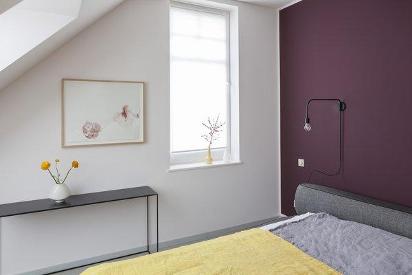 在卧室里,梅花功能墙弹出对一个灰色的床和一个柠檬黄色遥。简约的黑色的家具和简化照明完成空间。