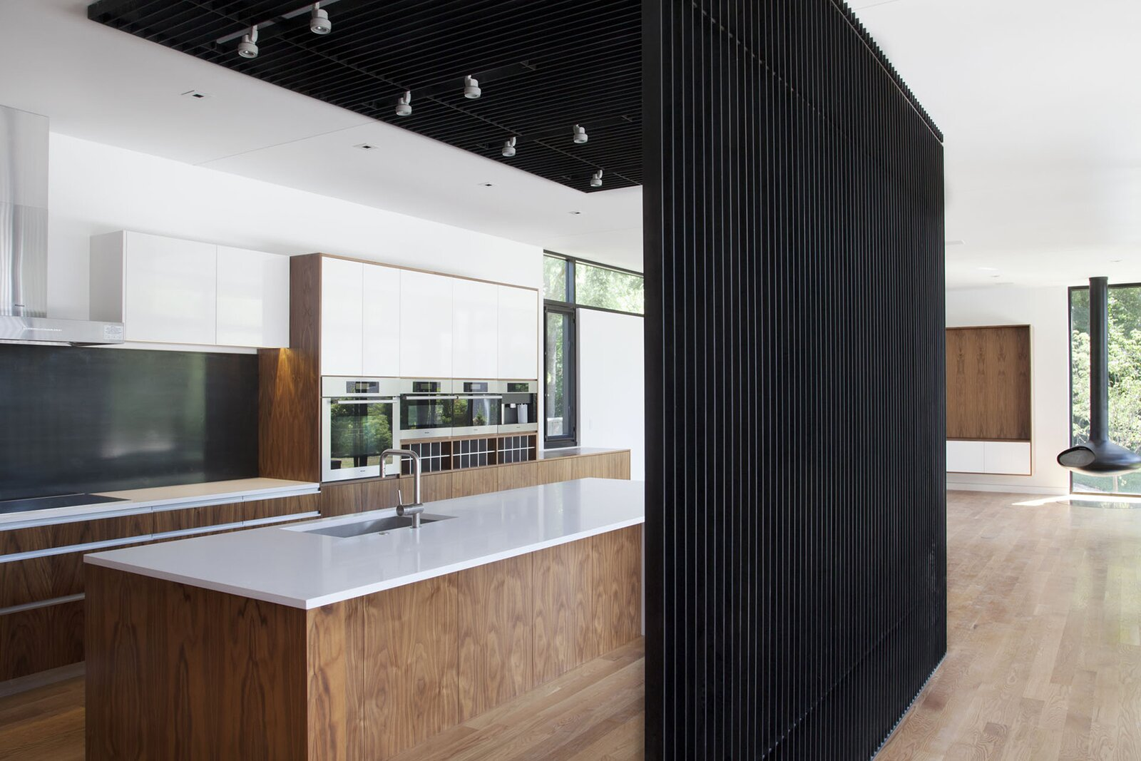 At the BauLinder Has by Hufft, a black vertical wood screen elegantly separates the kitchen and main living area.   Photo 21 of 30 in How the Pandemic Is Reshaping Interior Design So Far