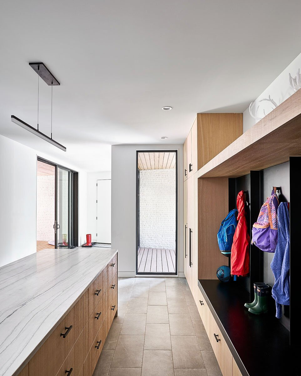 Simple details max out functionality in this mudroom at the Streamline House by Hufft, which features built-in storage for coats, shoes, and kids' backpacks. A large island with deep drawers adds additional storage space and a surface for folding laundry.  Photo 10 of 30 in How the Pandemic Is Reshaping Interior Design So Far