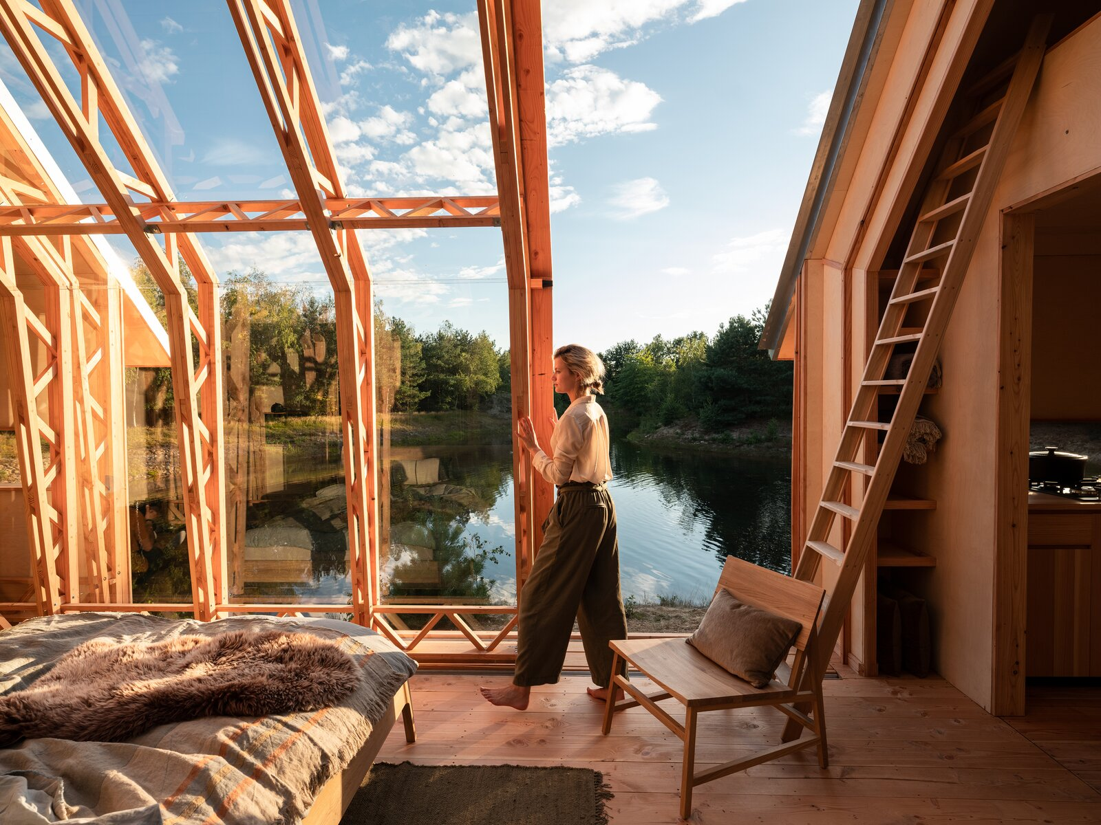 Bedroom, Chair, Medium Hardwood Floor, and Bed When the weather allows, the glass walls can be wheeled aside, leaving the living space open to the outdoors.   Photo 12 of 21 in This Ultra-Versatile Prefab Cabin Can Shed Its Layers of Wood and Glass