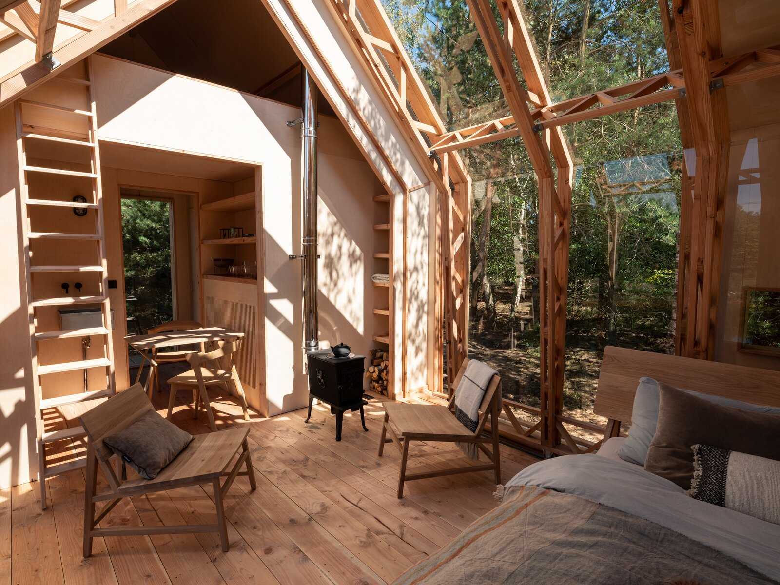 Living Room, Medium Hardwood Floor, Chair, and Wood Burning Fireplace The space is heated by a wood stove, with an option to install electric heating.   Photo 11 of 21 in This Ultra-Versatile Prefab Cabin Can Shed Its Layers of Wood and Glass