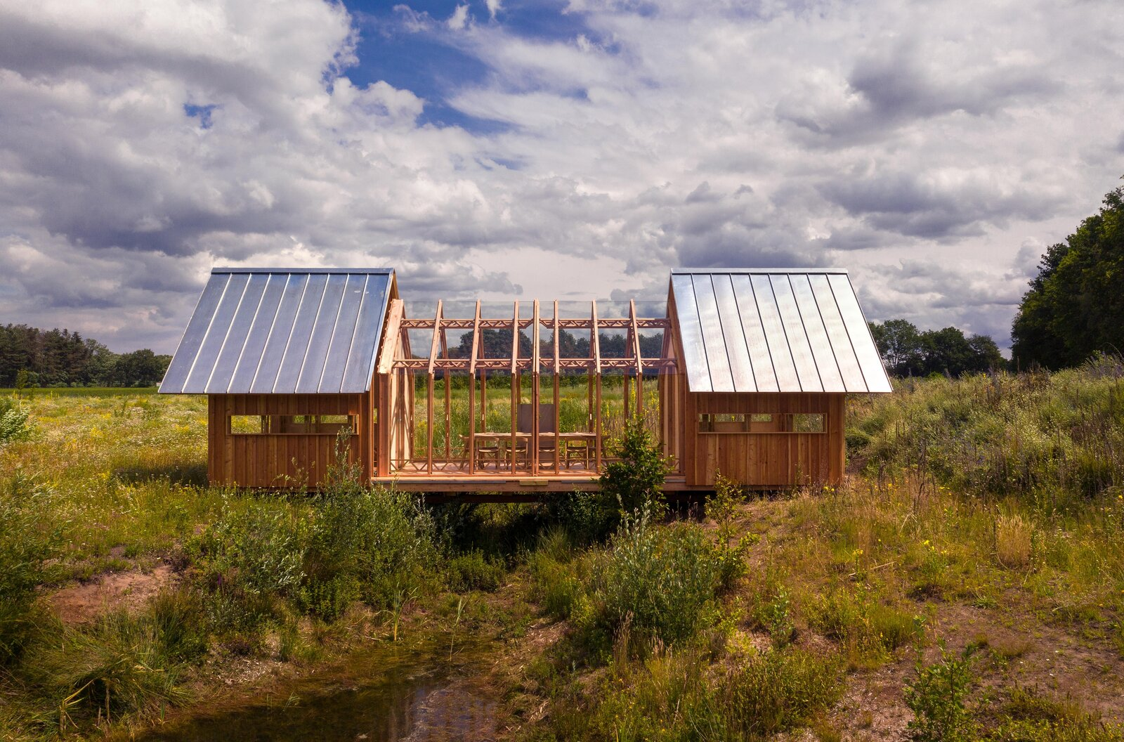 Here, the meeting space is protected from the elements but remains visually connected to the landscape.  Photo 17 of 21 in This Ultra-Versatile Prefab Cabin Can Shed Its Layers of Wood and Glass