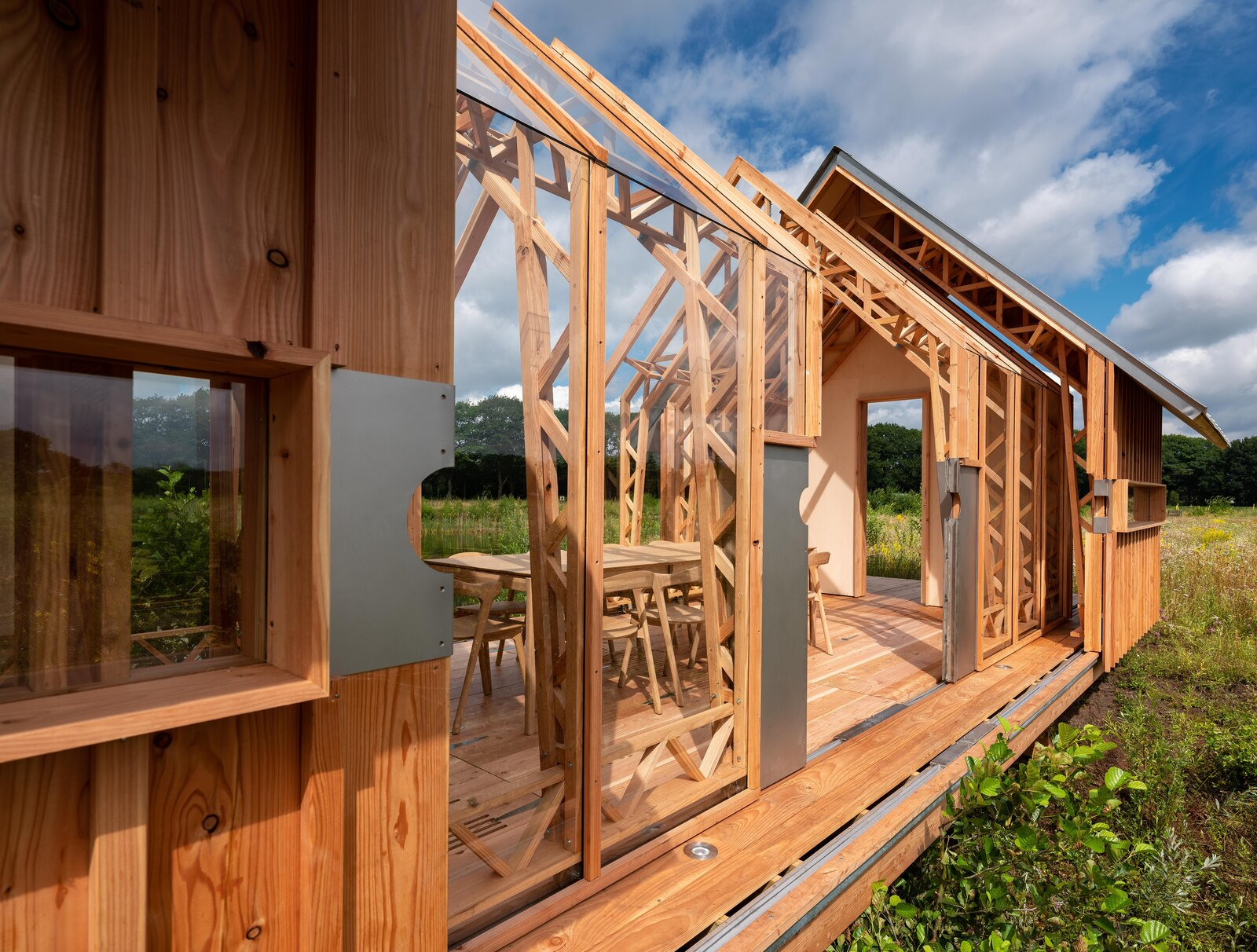 """Metal """"doors"""" with circular openings mark where to push the walls along their tracks. The structure relies on its side walls' wood trusses for structural integrity, as seen in railway stations.  Photo 6 of 21 in This Ultra-Versatile Prefab Cabin Can Shed Its Layers of Wood and Glass"""